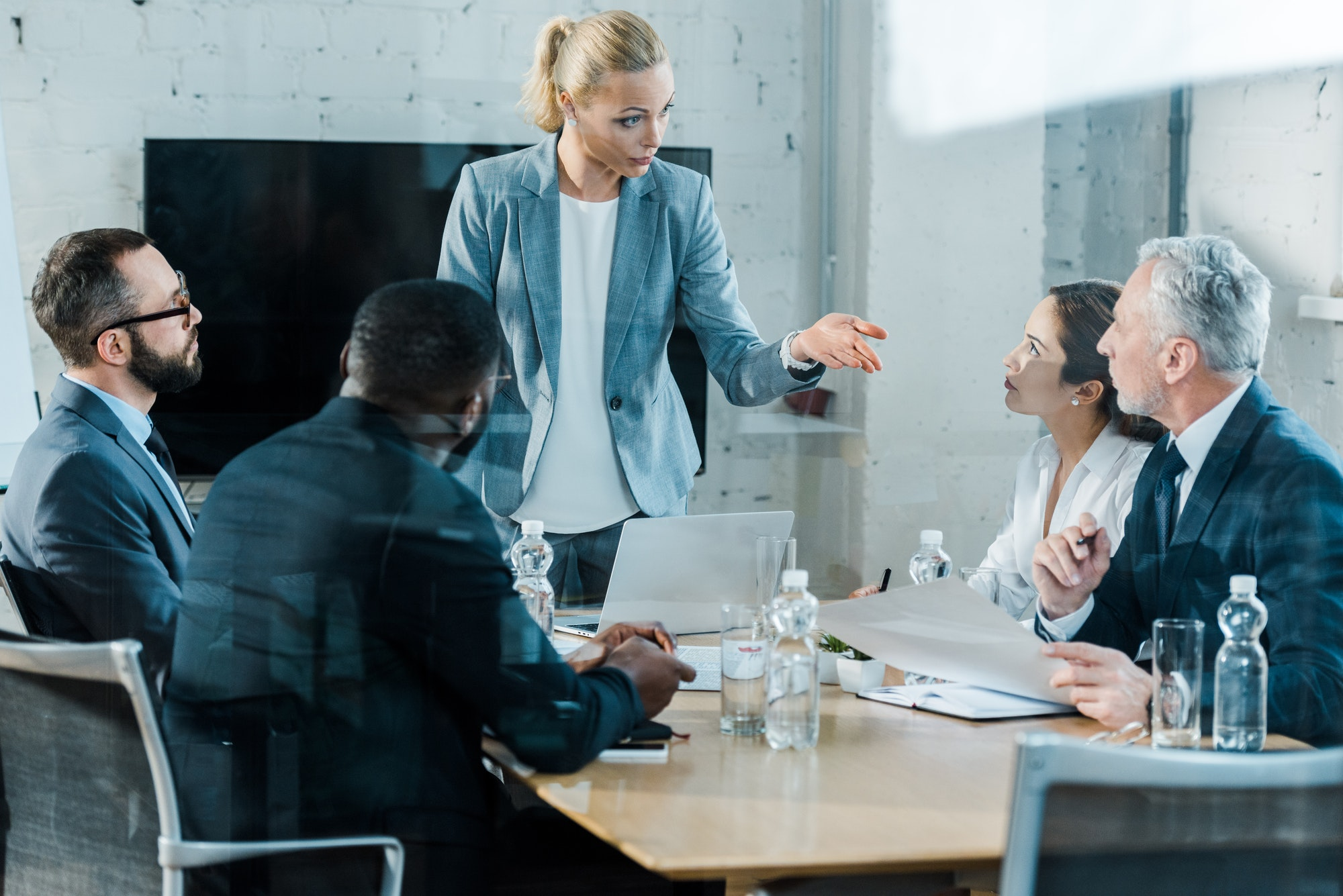 selective focus of business coach talking and gesturing in conference room near multicultural